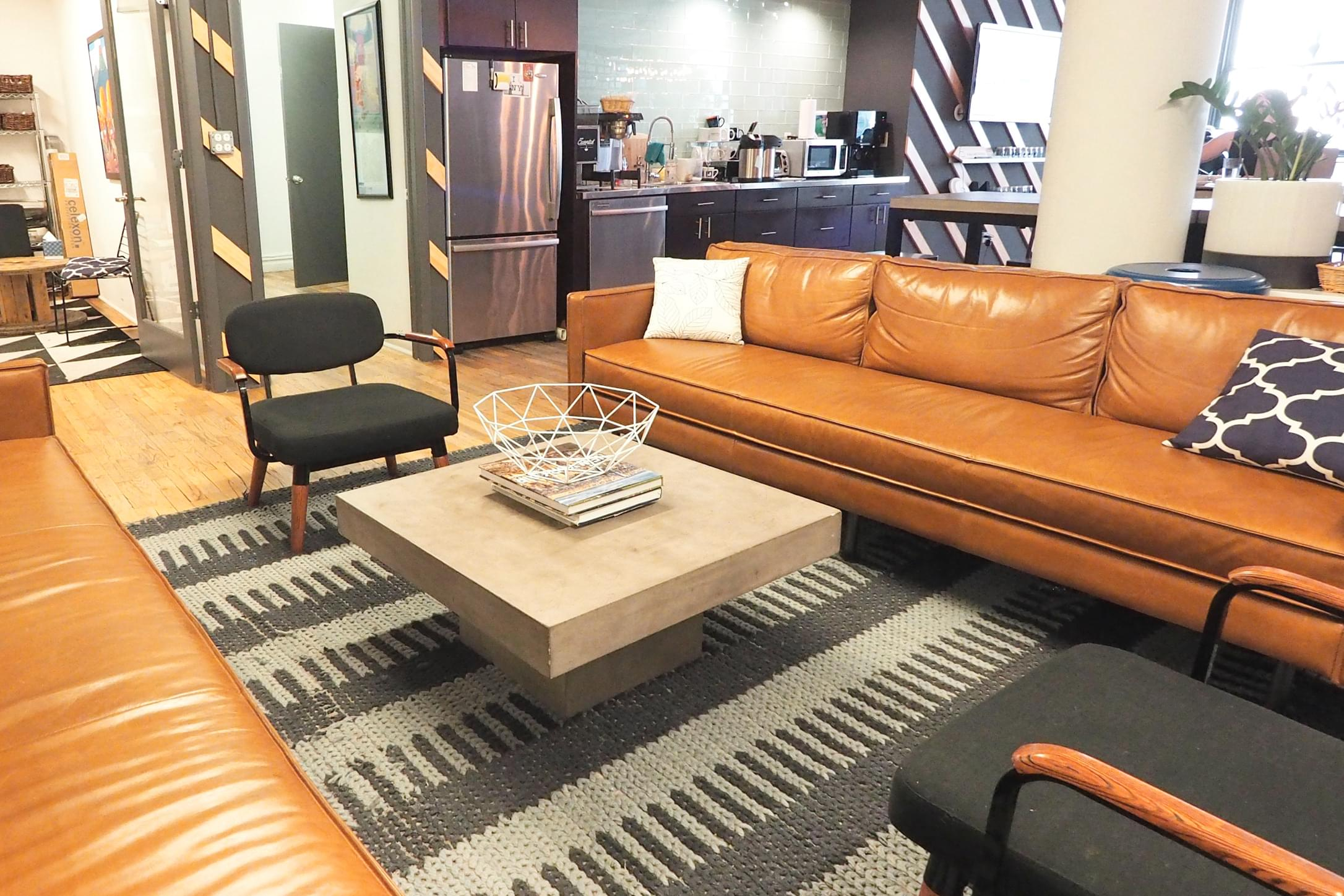 An office lounge area with long leather couch, coffee table, and kitchen in the background